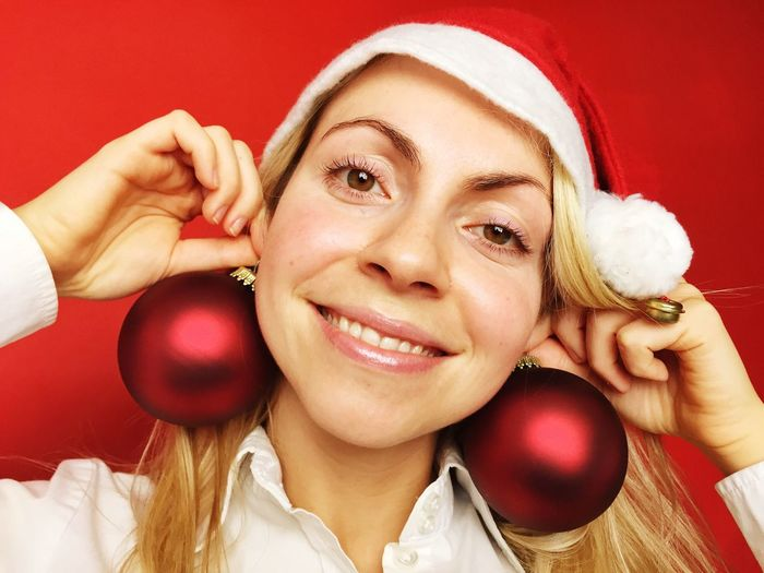 Close-Up Of Young Woman Holding Christmas Decorations