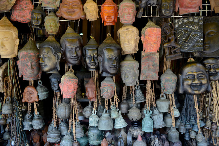 Buddha bust and bells hanging at market for sale