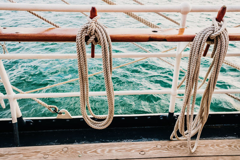 Close-up of rope tied to bollard on railing