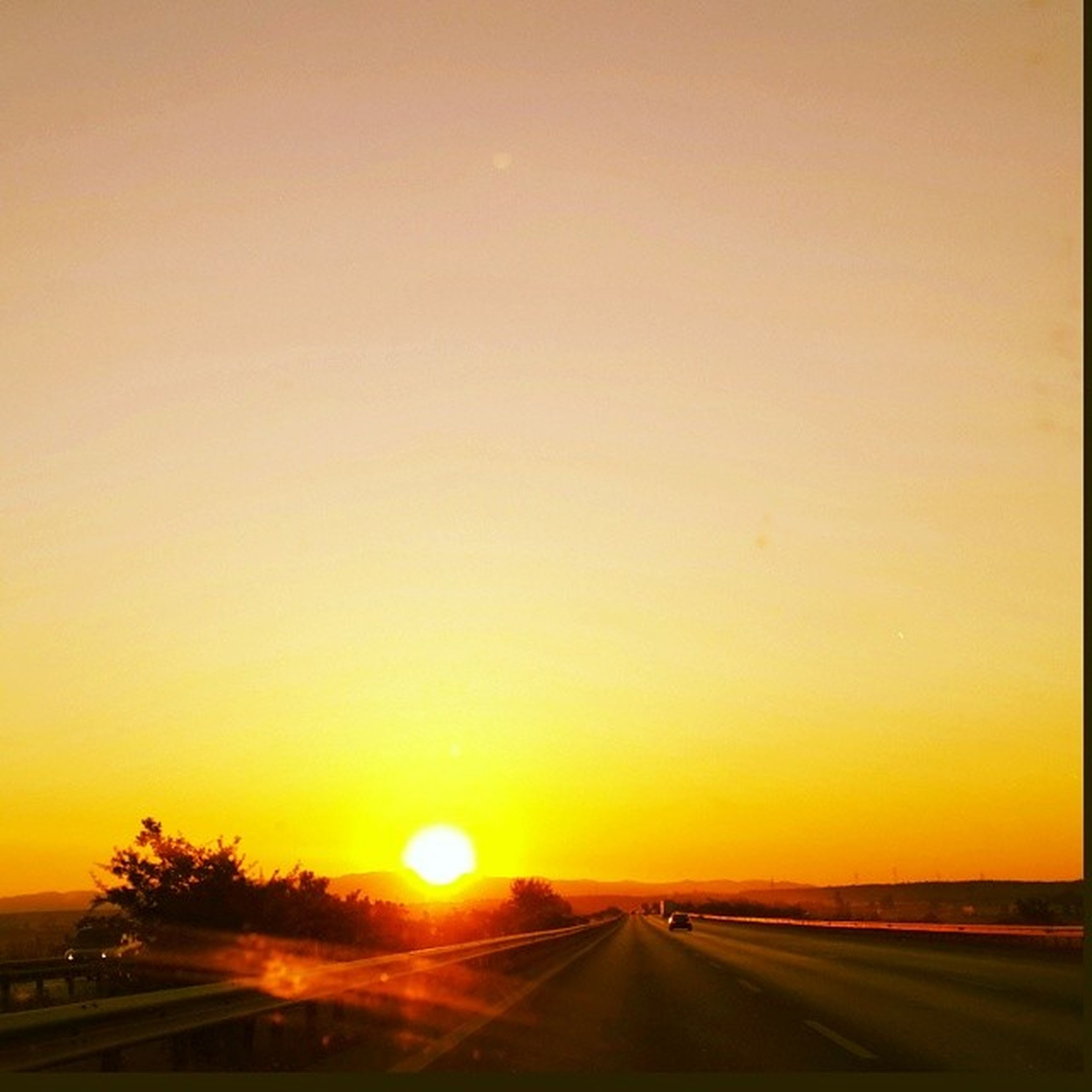 transportation, sunset, road, the way forward, car, diminishing perspective, orange color, sun, land vehicle, road marking, mode of transport, vanishing point, clear sky, copy space, sky, beauty in nature, nature, country road, street, scenics