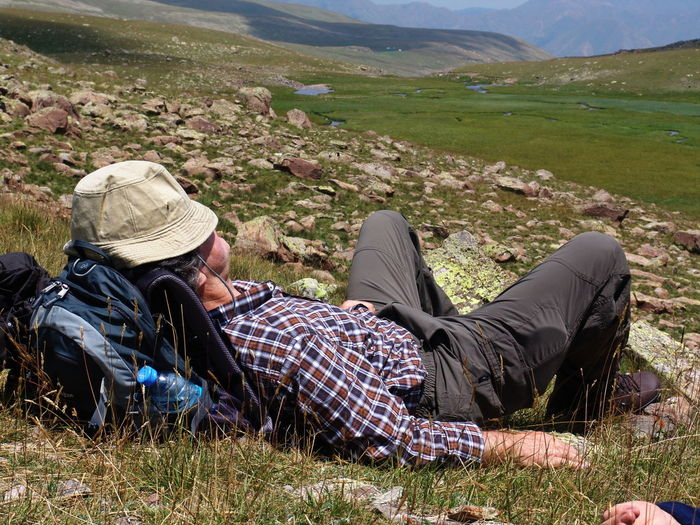 Adventure Beauty In Nature Day Field Full Length Grass Hiking Landscape Leisure Activity Lying Down Meadow Men Mountain Mountain Range Nature One Man Only One Person Outdoors Real People Relaxation Scenics Sitting Tranquil Scene Tranquility Vacations An Eye For Travel