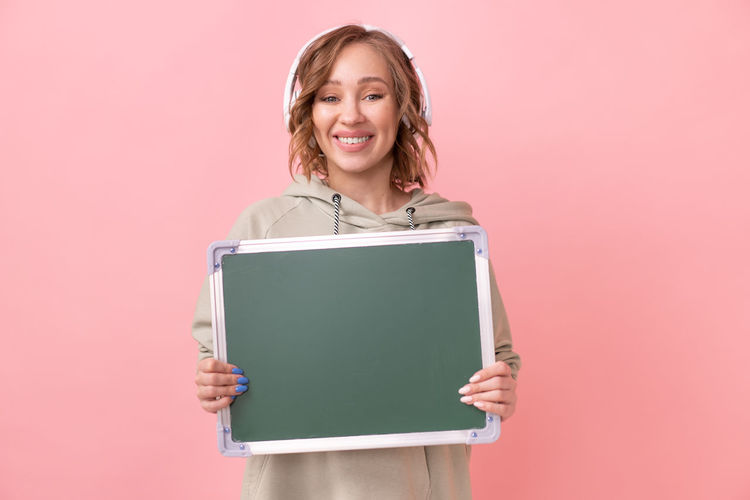 Portrait of smiling woman standing against pink background
