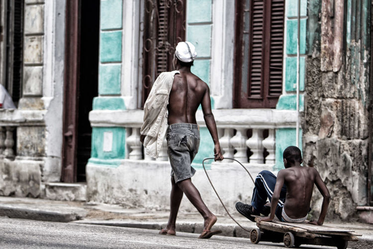 Rear view of men on street against buildings