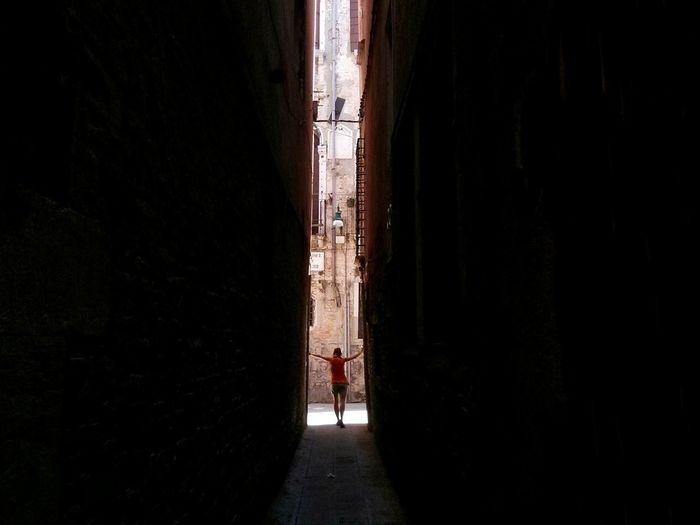 Rear view of people walking in alley