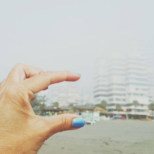 Cropped image of woman gesturing against buildings by beach