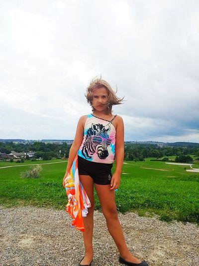 Portrait of girl standing on field against sky