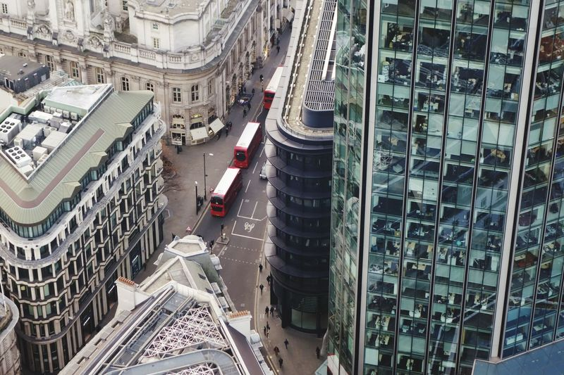 Red double decker busses cutting through a high angle view of London. The Big Smoke Bus City Cityscape High Angle View Street Architecture Building Exterior Built Structure Moving Urban Skyline Traffic Aerial View Vehicle