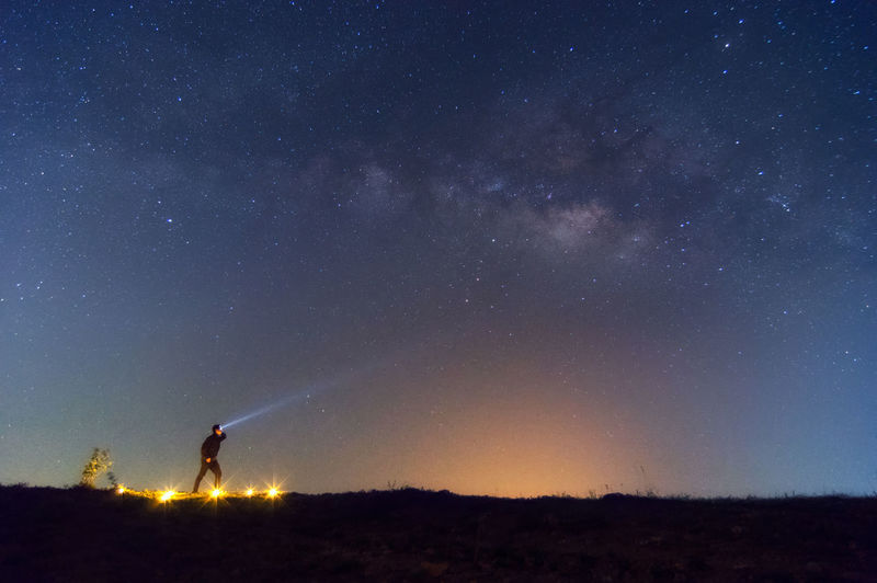 Man with flashlight on field against starry sky
