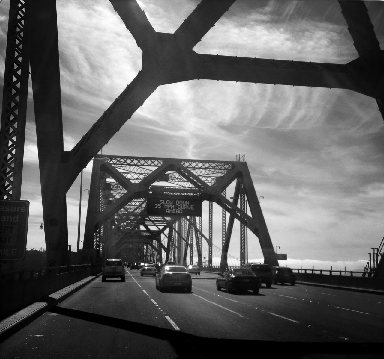 Cars on bridge against cloudy sky