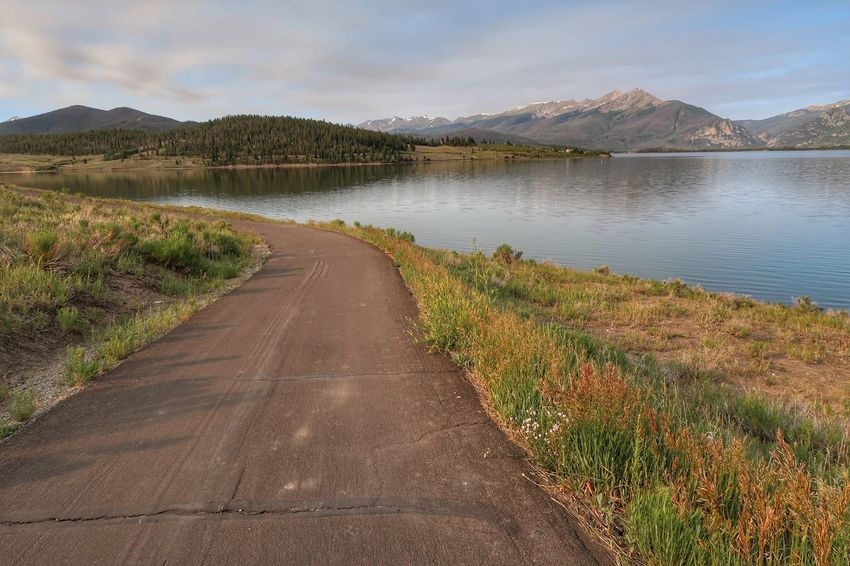 Landscape of road leading down to Dillon Reservoir with mountains in the background Landscape Colorado Dillon Reservoir Water Plant Sky Nature Beauty In Nature Cloud - Sky Direction Lake Day Road Transportation Diminishing Perspective Outdoors Non-urban Scene Tranquil Scene No People Scenics - Nature The Way Forward Tranquility Tree