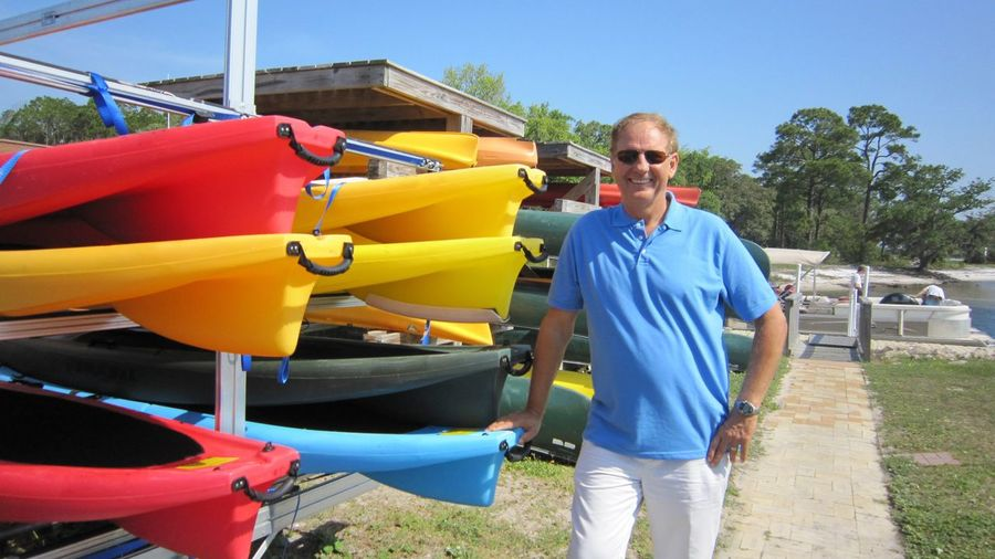 Portrait of smiling man standing by kayaks against clear blue sky