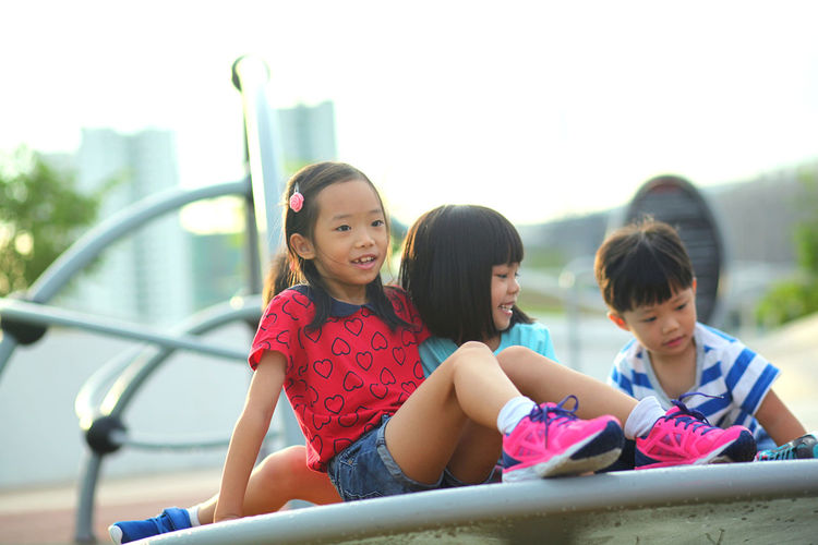 Cute Friends Playing On Outdoor Play Equipment In Playground