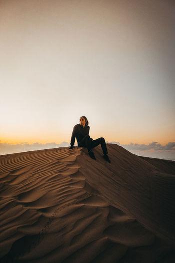 Man sitting on sand in desert against sky during sunrise