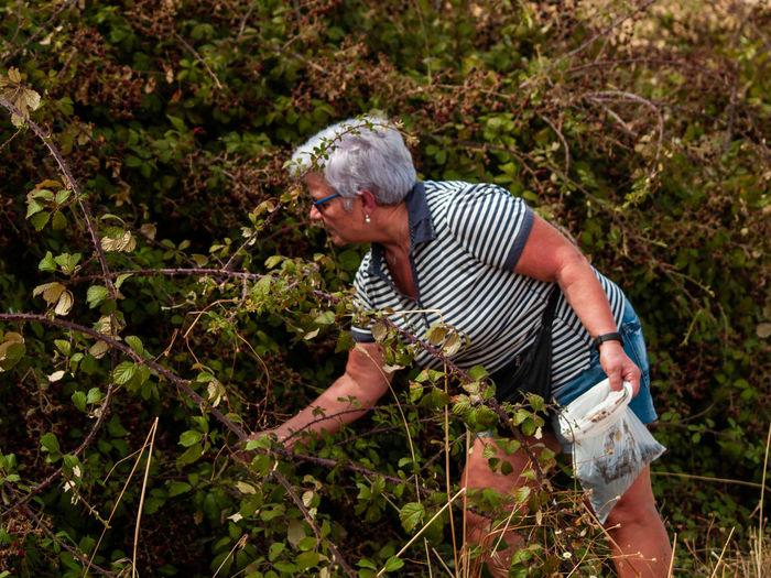 Senior woman gardening on field