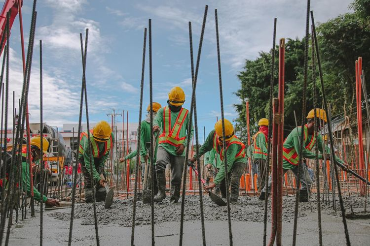 People working at construction site against sky