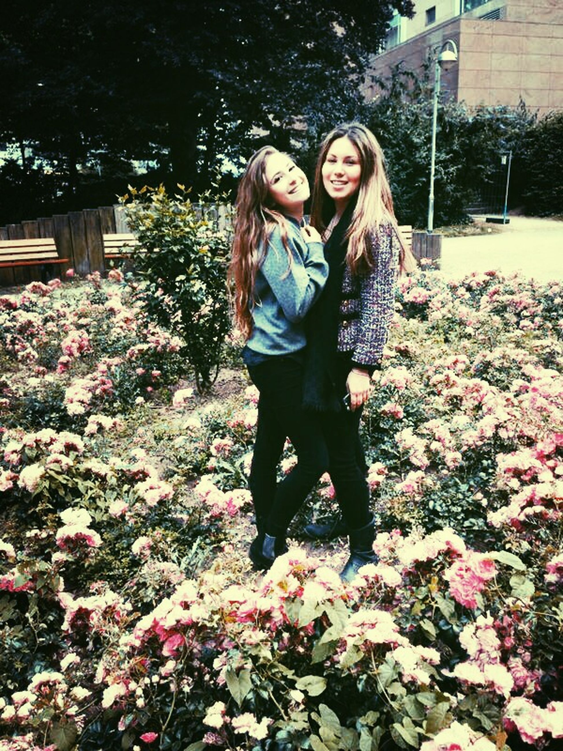 person, young adult, casual clothing, looking at camera, lifestyles, full length, flower, young women, portrait, smiling, leisure activity, standing, front view, happiness, three quarter length, plant, park - man made space