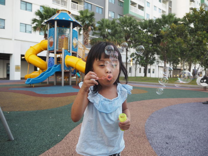 Cute Girl Blowing Bubbles In Playground
