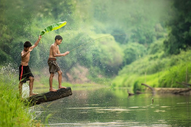 Shirtless boy with friend fishing while standing by river