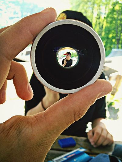 Cropped image man holding camera lens with view of friend