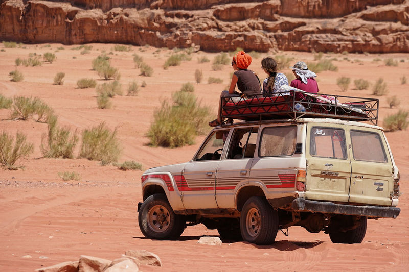 Wadi Rum Adult Adventure Arid Climate Day Desert Men Mode Of Transport Nature Outdoors People Real People Standing Togetherness Transportation Two People Weapon Women Young Adult