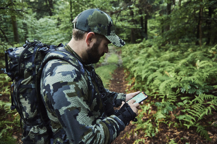 Man using mobile phone in forest