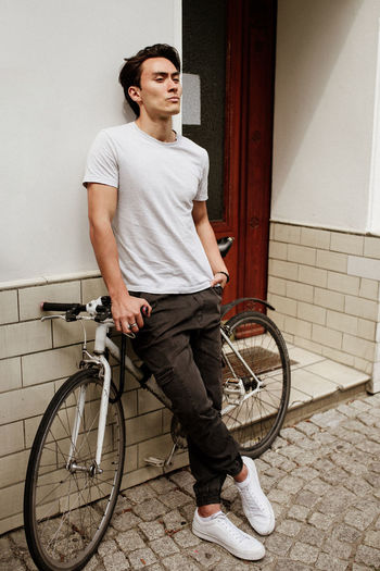 Young man with bicycle standing against door