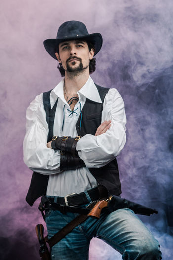 Handsome young man. This is an American cowboy. A vow to a white shirt, brown waistcoat and blue jeans. Black shoes on the feet. Carries a shtyapa, on a belt two pistols. The hair is of medium length; on the face is a beard and mustache. Authentic photo. Culture of America. Cowboy Wild West America American Gun National Authentic Moments Lifestyles Lifestyle One Person Candid Authentic Hat Three Quarter Length Smoke - Physical Structure Front View Beard Facial Hair Clothing Real People Looking At Camera Casual Clothing Young Adult Portrait Young Men