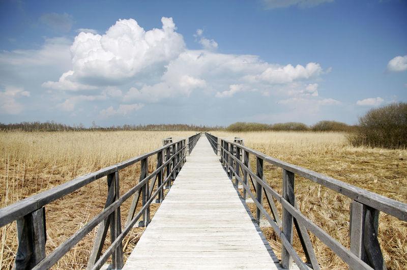 Wooden footbridge on field against sky