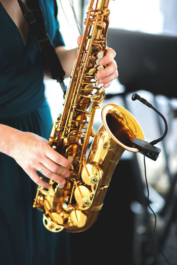 Midsection Of Woman Playing Saxophone At Music Concert