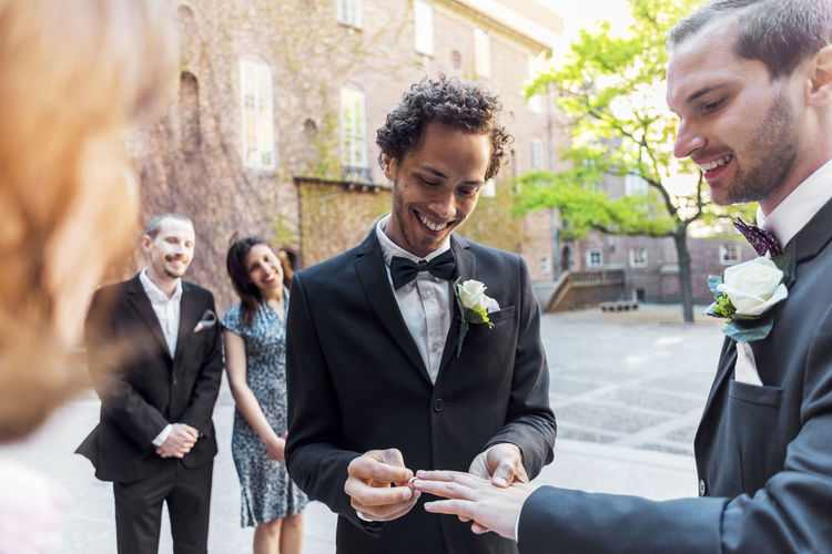 Gay couple exchanging rings during wedding ceremony