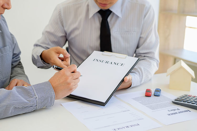 Midsection Of Real Estate Agent With Client Holding Form At Office