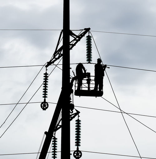 Cable Cloud - Sky Complexity Connection Day Electricity  Electricity Pylon Fuel And Power Generation Hanging Low Angle View Maintenance Engineer Manual Worker Occupation Outdoors People Power Line  Power Supply Real People Sky Technology Telephone Line Working