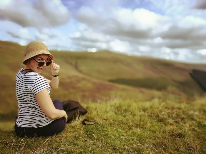 Rear View Portrait Of Woman Sitting On Grassy Field Against Cloudy Sky