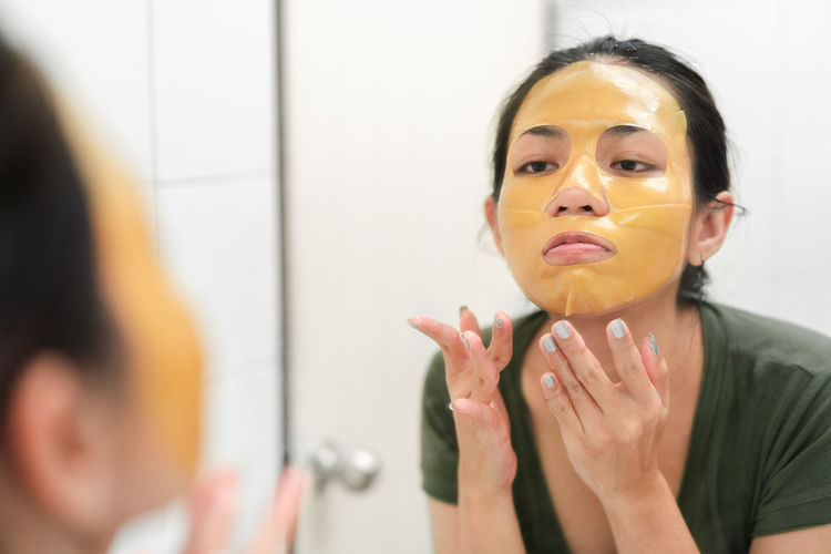 Close-up of woman applying facial mask
