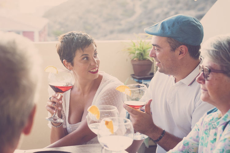 Friends Talking While Holding Drinks On Balcony