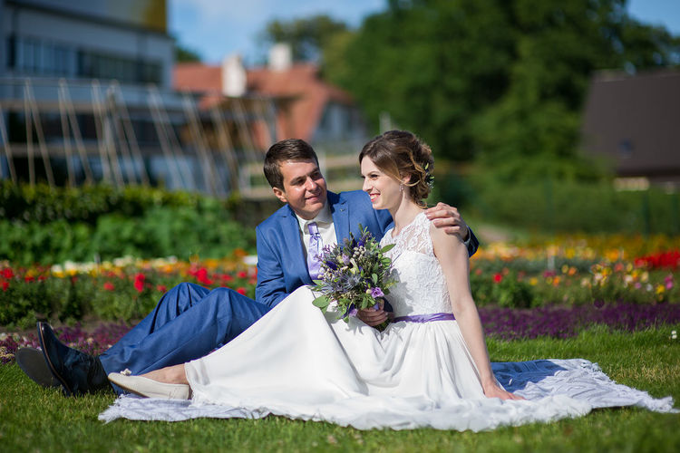 Bride And Bridegroom Sitting On Picnic Blanket At Park
