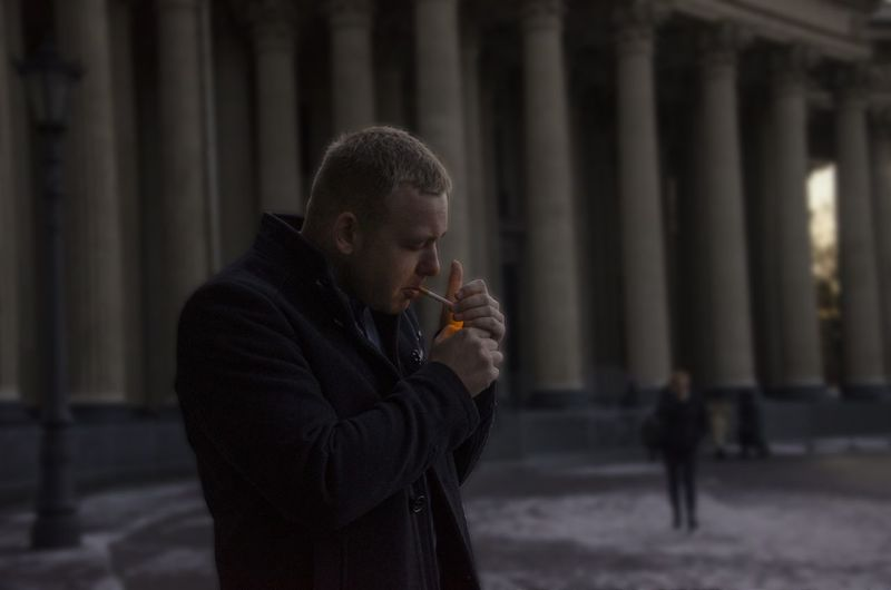 Young man igniting cigarette while standing against columns during winter