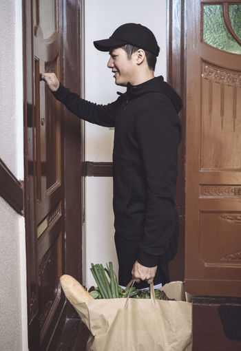 Side view of young man standing against door at home