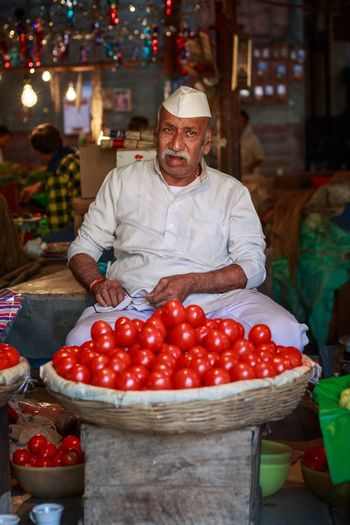 The Tomato Merchant. Pune, India. Portrait Looking At Camera One Person Red Adults Only Men Business Occupation Working Standing Business Finance And Industry Food Senior Adult Manual Worker One Man Only People Freshness Indoors  Adult Only Men Light And Reflection The Portraitist - 2018 EyeEm Awards