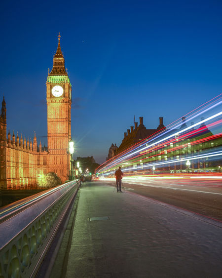 Light trails on westminster bridge by big ben in city at night