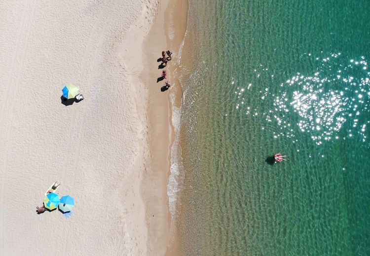 High angle view of people at beach on sunny day