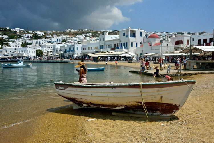 cityscape near the beach and rear view of a woman with hat standing near a boat and watching her mobile Nautical Vessel Water Transportation Mode Of Transportation Building Exterior Sky Architecture Built Structure Nature Moored Sea Day City Real People One Person Land Cloud - Sky Harbor Men Outdoors Woman Beach Mykonos,Greece Sandy Beach Cityscape Chora Village Lifestyles Travel Tourist Hat Mobile Seafront Greek Architecture Panoramic View Street Photography