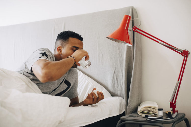Young man using mobile phone on bed at home