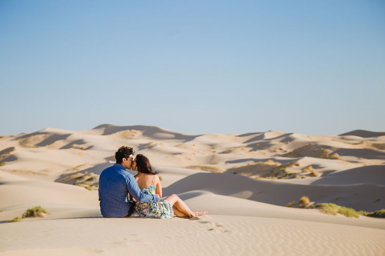 Rear view of couple kissing while sitting on sand at desert against sky
