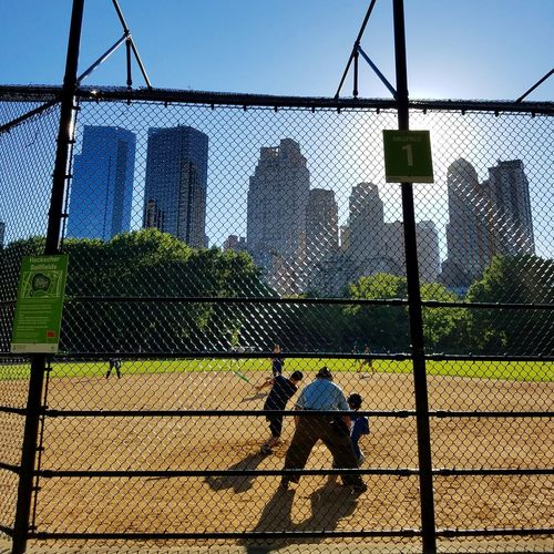 People playing baseball seen through chainlink fence