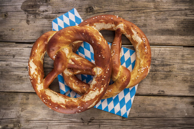 snacks on wooden view Breze Jaune Oktoberfest Wooden Table Baked Bayern Bayrisch Blau Weiss Bread Brezel Close-up Fast Food Food Food And Drink Freshness German Food Pretzel Ready-to-eat Serviette Snack Still Life Table Unhealthy Eating Wood - Material