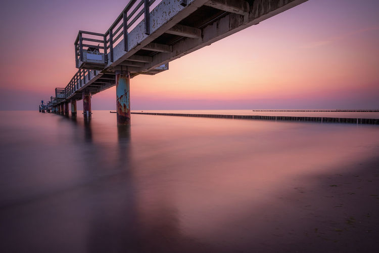 Bridge over sea against sky during sunset