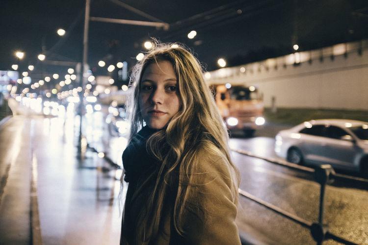 Portrait of beautiful woman standing on illuminated car at night