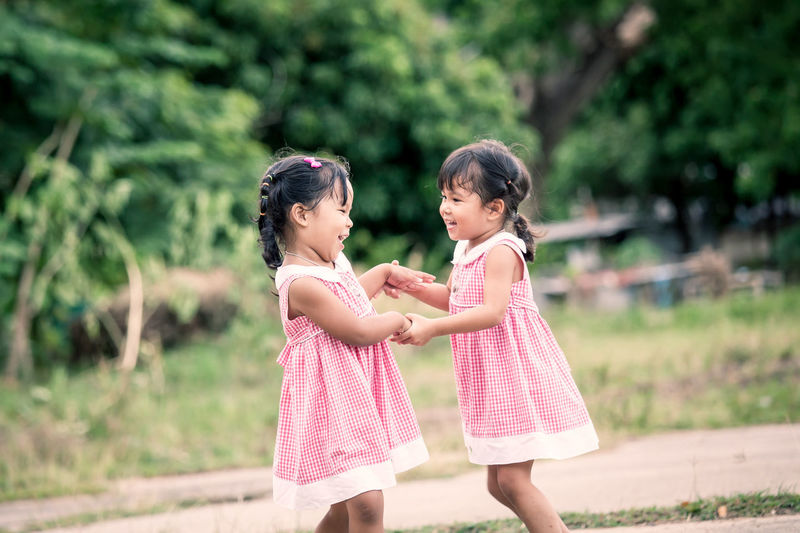 Child two girls having fun to play together in the park,vintage color filter Dancing Fun Happy Innocence Love Nature Recreation  Sister Activity Adorable Child Cute Daughter Enjoying Life Girls Leisure Activity Outdoor Outdoors Park People Playing Smile Togetherness Twin Two People