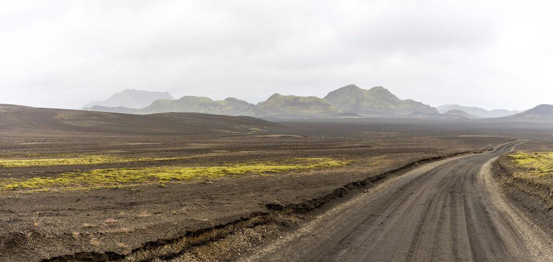 Dirt road passing through landscape against sky